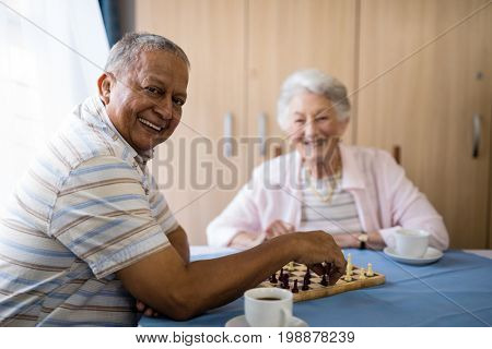 Smiling senior man playing chess with friend while sitting at table in nursing home