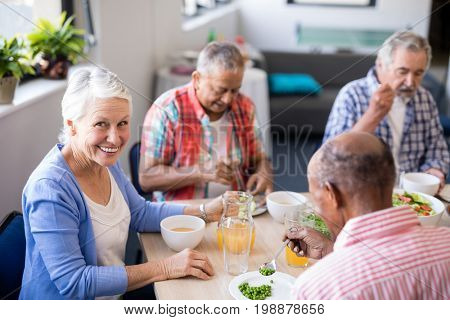 Portrait of senior woman sitting with friends while having breakfast at table in nursing home