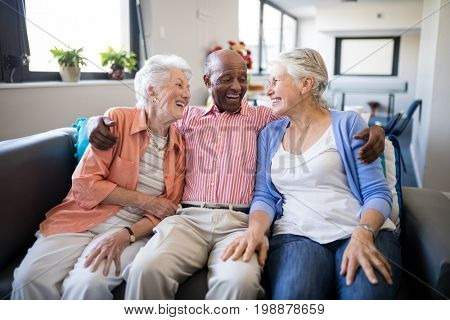 Smiling senior man sitting with arm around over female friends on sofa at nursing home