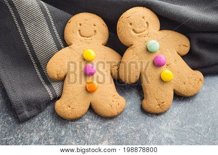 Two sweet gingerbread men on old kitchen table. Xmas gingerbread. Laughing gingerbread man.