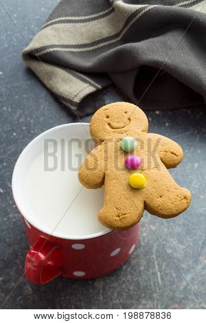 Two gingerbread man and mug of milk on old kitchen table. Xmas gingerbread. Laughing gingerbread man.