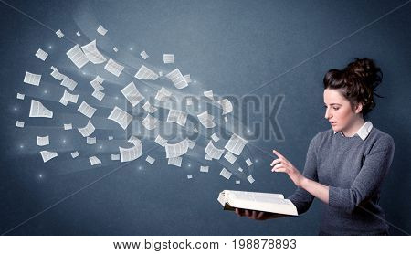 Casual young woman holding book with pages flying out of it