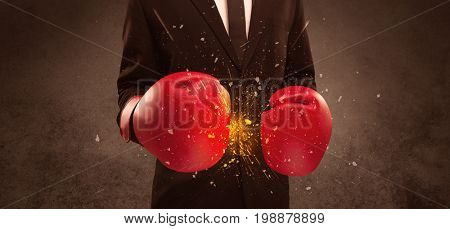 A strong sales person breaking something into pieces with red boxing gloves concept illustrated with glowing residue flying in the air.