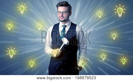 Better-looking businesman holding tool with idea bulbs concep