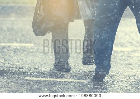 People running away through puddle at street during heavy rain