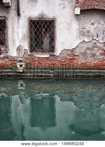 old decaying building in venice with windows reflected in the canal and crumbling bricks and plaster