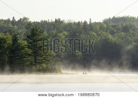 Silhouette of two people in boat floating fishing in morning mist rising off lake. Wilderness sport and adventure landscape. Peaceful sunrise scene.