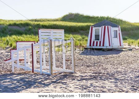 Abandoned lifeguard stand on its side and beach cabana on empty beach just before sunset. Summer ending concept.