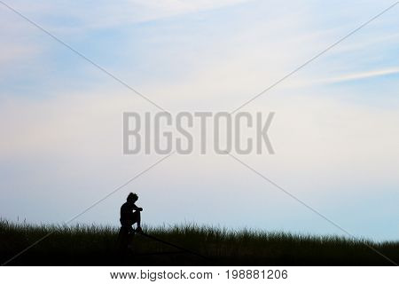 Silhouette of young teen man curly hair sitting on post in field deep in thought beneath a pastel morning or evening sky. Life contemplation concept and background with space for text.