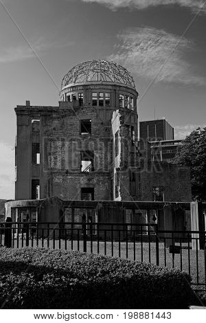 Black and white photo of the Atomic bomb dome in Hiroshima Japan on a sunny day with blue sky and green grass. First A-bomb was dropped in Hiroshima this ruin was left standing.