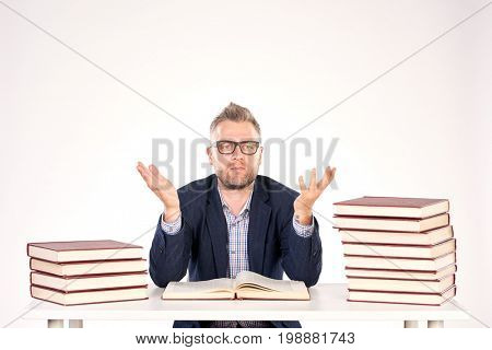 Portrait of middle-aged professor sitting at desk with book heaps on it