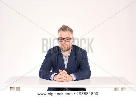 Portrait of pensive professor sitting at desk