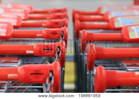 Red handles of shopping trolleys standing in row. Shopping trolley handles close-up.