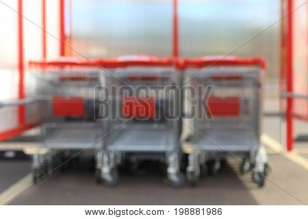 Blurred shopping background. Unfocused shopping trolleys with red handles on backdrop.
