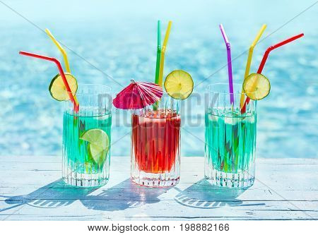 Glasses with mint and cherry juice on the side of a swimming pool with blue water in the background.