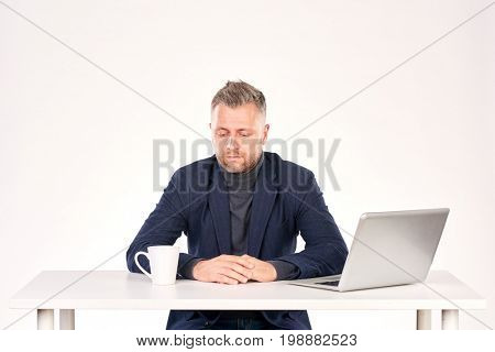 Portrait of middle-aged businessman sitting at office desk with laptop on it
