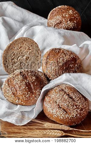 Integral bread buns with various seeds on white kitchen towel.