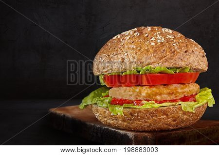 Hamburger made with meat lettuce tomato ketchup and seeds bun on black background.