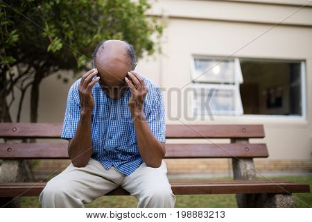 Upset senior man sitting with head in hands on bench against nursing home