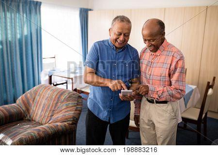 Smiling senior male friends using mobile phone at nursing home