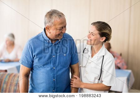 Smiling senior man looking at young female doctor at retirement home