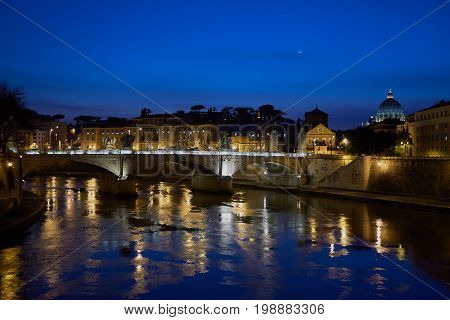 Night view of Rome from Tiber riverbank to Sant Angelo bridge and Vatican city.