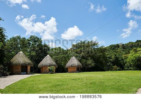 Tropical huts on an island with conical thatch roofs weaved out of coconut palm tree fronds. Bright daylight blue sky with puffy Cumulus clouds. Copy space.