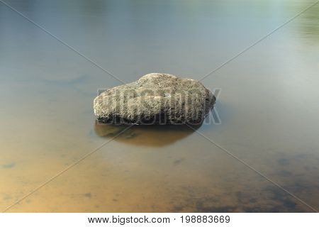 Smooth boulder lies in the water on river bank low tide long exposure soften appearance of water.
