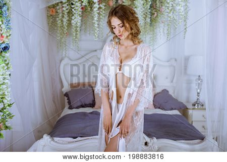 Beautiful sexy lady in elegant white robe. Close up fashion portrait of model indoors. Beauty brunette woman. Attractive female body in lace lingerie. Closeup fashionable naked girl in underwear