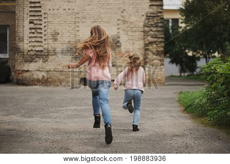 photo of two girls with long hair running away