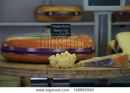 Traditional Dutch cheeses on display on a market stall. Text on tag: product information in Dutch old farmers cheese.