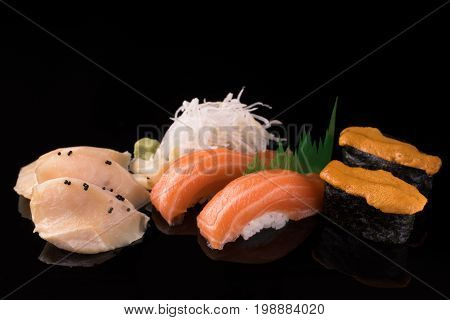 Fresh and delicious sushi set served on a black reflective surface includes salmon nigiri sushi white tuna sashimi and uni gunkan (sea urchin). On the side daikonwasabi and ginger. Close up.