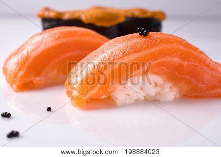 Two pieces of Japanese salmon nigiri sushi piece of uni gunkan on a white reflective surface decorated black tobiko.