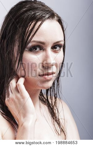 Beauty Concepts and Ideas. Closeup Portrait of Caucasian Sensual Brunette Touching Neck and Showing Wet and Shining Skin and Wet Hair. Creative Makeup. Against Grey. Vertical Image Composition