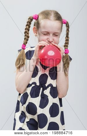Portrait of Funny Caucasian Blond Girl With Pigtails Posing in Polka Dot Dress Against White. Blowing Up Red Heart Shaped Air Balloon. Vertical Image