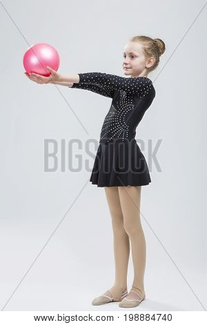 Full Length Portrait of Caucasian Female Rhythmic Gymnast In Professional Competitive Black Sparkling Suit Posing With Ball in Studio On White. Vertical Image Orientation