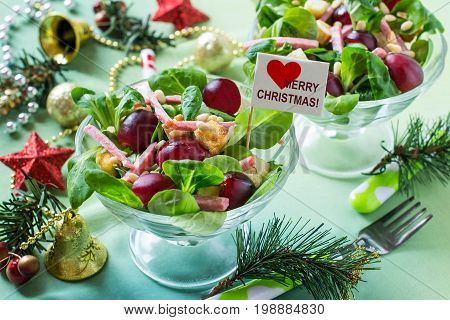 Delicious festive salad with fresh corn salad grapes sausage croutons and nuts Siberian pine in glass vases. Bright color and taste. Colorful salad for Christmas. Selective focus