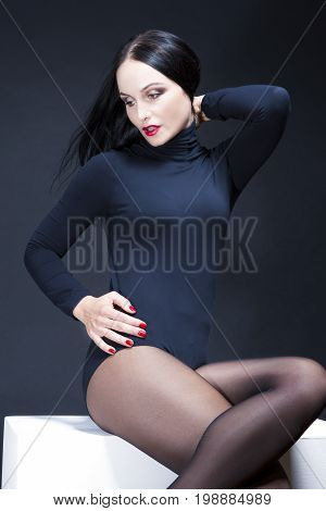 Beauty Concepts and Ideas. Natural Studio Portrait of Mid Aged Sexy Sensual Caucasian Brunette Woman Posing in Black Body Suit.Vertical Image