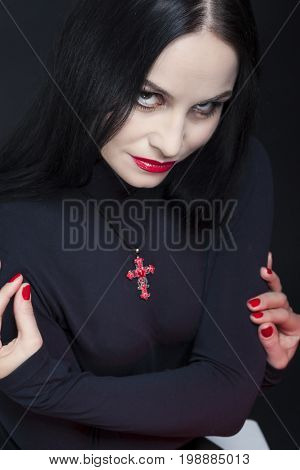 Closeup Portrait of Passionate and Sexy Mid-Aged Caucasian Brunette Woman Posing in Studio in Black Body Suit Against Black. Vertical Image Composition