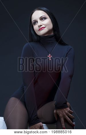 Portrait of Passionate and Sexy Mid-Aged Caucasian Brunette Woman Posing in Studio in Black Body Suit Against Black. Vertical Image Orientation