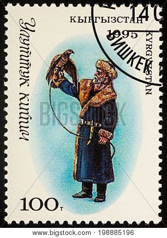 Moscow Russia - August 07 2017: A stamp printed in Kyrgyzstan shows man-hunter in traditional Kyrgyz clothes (fur coat) with a falcon series