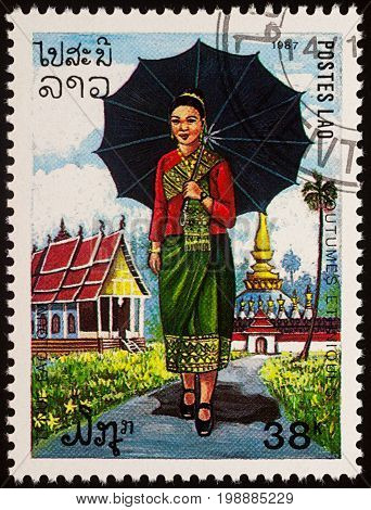 Moscow Russia - August 06 2017: A stamp printed in Laos shows a woman in national Lao dress with umbrella against the backdrop of a Buddhist temple series