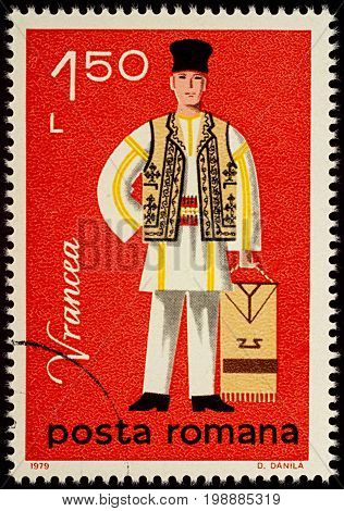 Moscow Russia - August 08 2017: A stamp printed in Romania shows young man in Romanian folklore costume Vrancea county series