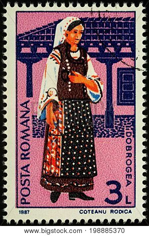 Moscow Russia - August 07 2017: A stamp printed in Romania shows young woman in Romanian national costume Dobrogea region series