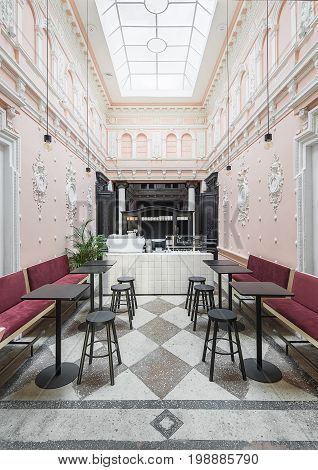 Coffee zone in the antique restaurant with white stucco molding on the pink walls and large window on the ceiling. There are red sofas, tiled rack with coffee machines, sideboard, tables and stools.