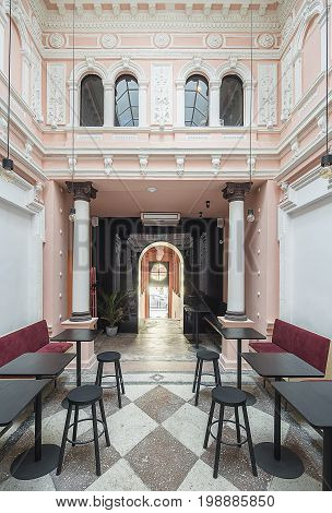 Antique restaurant with white stucco molding on the pink walls and a tiled floor. There are red sofas, black tables and stools, columns, arch entrance with a stairway, hanging lamps, windows. Indoors.