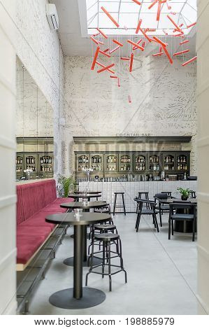 Bar with light textured walls and a large window on the ceiling. There are red sofas, black round tables, dark stools and chairs, plants, tiled bar rack, shelves with bottles, hanging red lamps.