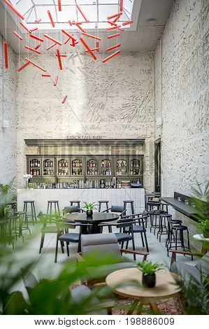 Stylish bar with light textured walls and a large window on the ceiling. There are round wooden tables, stools and chairs, many plants, tiled bar rack, dark shelves with bottles, hanging red lamps.