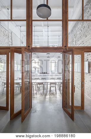 Cafe with shabby light walls and a large wooden partition with windows and glass doors. There are wide white tables with chairs, arch windows, hanging round lamps, frames on the walls. Indoors.