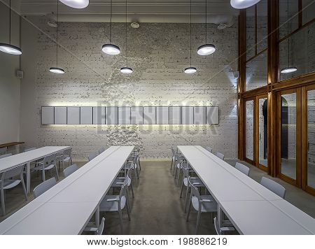 Luminous hall in the cafe with shabby light walls and gray floor. There are white tables with chairs, frames on the wall, hanging round lamps, large wooden partition with windows and glass doors.
